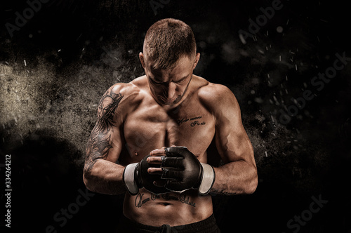 Mixed martial artist posing on a black background Wallpaper Mural