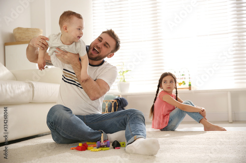Vászonkép Unhappy little girl feeling jealous while father spending time with her baby bro