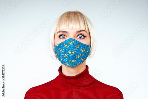 Fototapeta Shocked, surprised woman wearing handmade face mask. Copy, empty space for text obraz