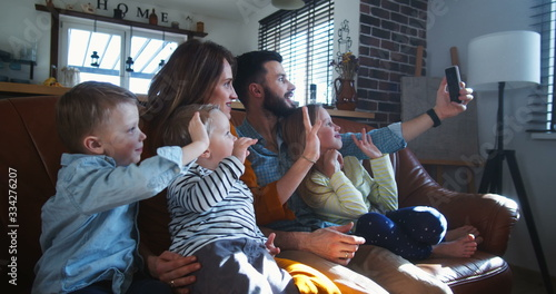 фотография Happy young Caucasian family with three kids wave to friends talking during smartphone video call at home slow motion