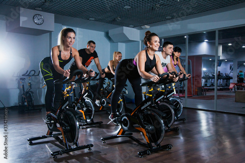Cycling class in fitness club, group of fit people spinning on cardio machine Fototapeta