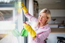Portrait Of Senior Woman Cleaning Windows Indoors At Home.