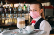 canvas print picture - A female Waiter of European appearance in a medical mask serves Latte coffee.