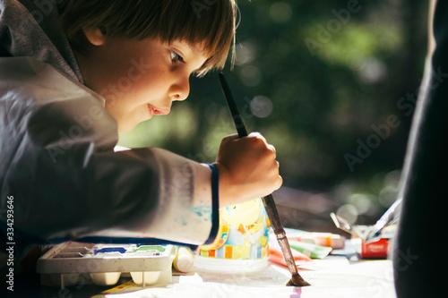 Obraz Niño haciendo actividades artisticas con pincel y pinturas - fototapety do salonu