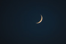 Thin Yellow Crescent Moon On A Dark Blue Background