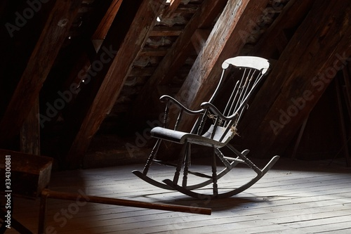Photo Old rocking chair on a dim attic window light