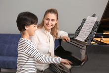 Private Music Teacher Giving Piano Lessons To Little Boy