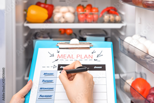 Photo Woman making meal plan in kitchen