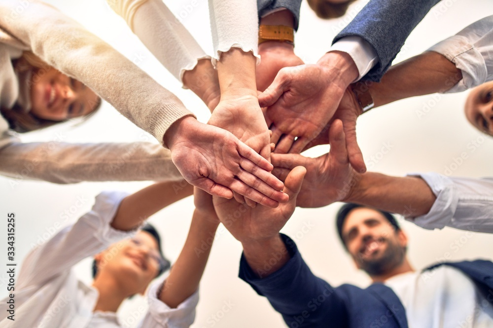 Fototapeta Group of business workers standing with hands together at the office