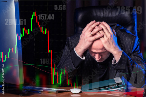Photo The man clutched his head with both hands against the background of stock quotes