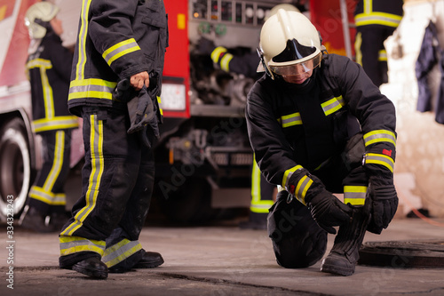 Professional firefighters with uniforms and protective helmets getting ready for action Canvas Print