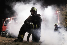 Team Of Professional Firefighters Holding Water Hose In Front Of A Firetruck With Smoke In The Air. Half Silhouette.