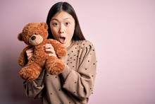 Young Asian Woman Hugging Teddy Bear Stuffed Animal Over Pink Isolated Background Scared In Shock With A Surprise Face, Afraid And Excited With Fear Expression