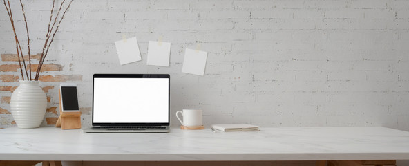Cropped shot of minimal workspace with mock-up laptop, smartphone, decorations and copy space
