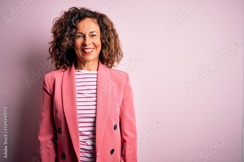 Fotografía Middle age beautiful businesswoman wearing elegant jacket over isolated pink background with a happy and cool smile on face