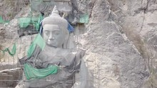 Aerial Sliding Shot Of The Giant Buddha Statue With Bamboo Scaffolding In Construction , Carved Into The Rock Face Of The Hill