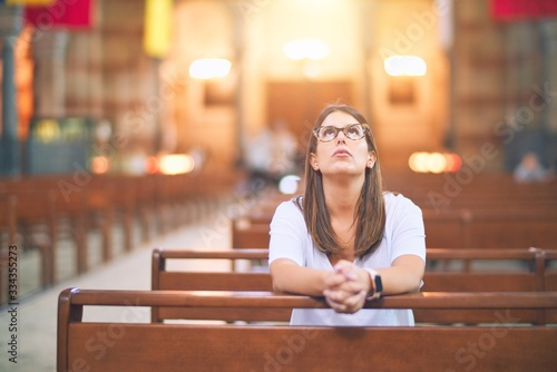 Young beautiful woman praying on her knees in a bench at church Fototapete