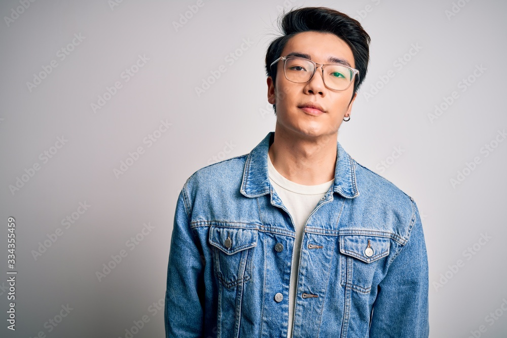 Fototapeta Young handsome chinese man wearing denim jacket and glasses over white background Relaxed with serious expression on face. Simple and natural looking at the camera.
