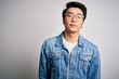Young handsome chinese man wearing denim jacket and glasses over white background Relaxed with serious expression on face. Simple and natural looking at the camera.