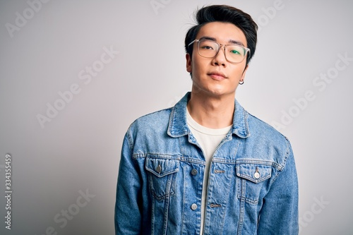 Fototapeta Young handsome chinese man wearing denim jacket and glasses over white background Relaxed with serious expression on face. Simple and natural looking at the camera. obraz