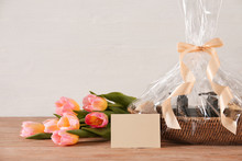 Basket With Gifts And Flowers For Mother's Day On Table