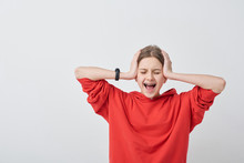 Shocked Or Hysteric Teenage Girl In Red Hoodie Touching Head And Screaming