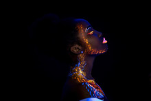 Unusual Portrait Of Beautiful African Fashion Woman In Neon UF Light. Attractive Young Model Girl With Fluorescent Creative Psychedelic Make-up, Body-art