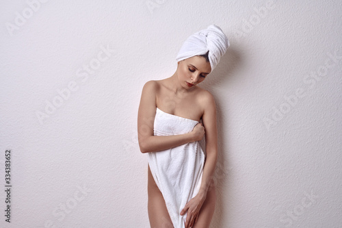 Alluring young naked woman covering her breasts and front of her torso with a fr Wallpaper Mural