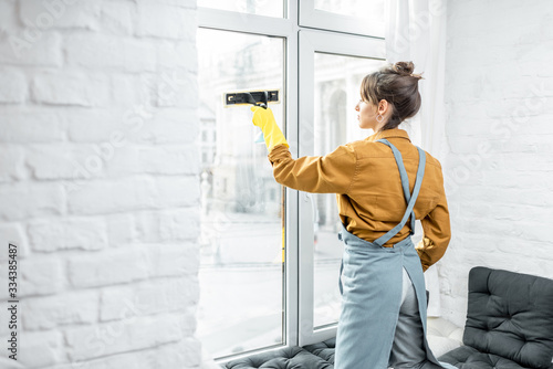 Fotografia Beautiful young housewife in working clothes washing windows by professional too
