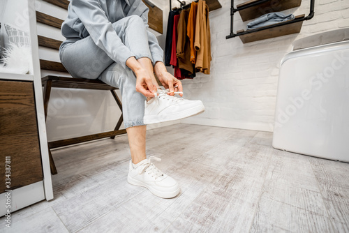 Vászonkép Woman wearing white sneakers in the wardrobe or small clothes store