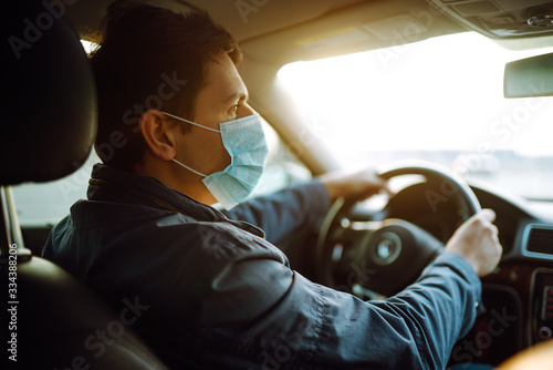 Obraz Young man in protective sterile medical mask driving car. The concept of preventing the spread of the epidemic and treating coronavirus, pandemic in quarantine city. Covid -19. - fototapety do salonu