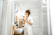 Young And Beautiful Woman Standing With Hairbrush During Some Hygiene Procedures In The White Modern Bathroom