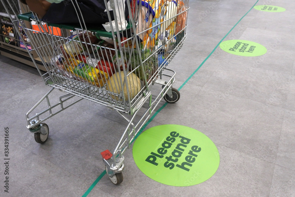 Fototapeta Social distancing marks on supermarket floor intended to stop or slow down the spread of a contagious Coronavirus (COVID-19)  disease.