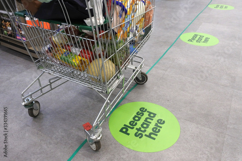 Foto Social distancing marks on supermarket floor intended to stop or slow down the spread of a contagious Coronavirus (COVID-19)  disease