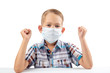 a boy in a medical mask sits at a table, protection during a pandemic from coronavirus