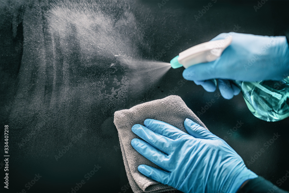 Fototapeta Surface home cleaning spraying antibacterial sanitizing spray bottle disinfecting against COVID-19 spreading wearing medical blue gloves. Sanitize surfaces prevention in hospitals and public spaces.