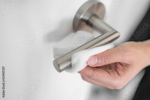 Obraz Coronavirus COVID-19 Prevention cleaning woman wiping doorknob with antibacterial disinfecting wipe for killing corona virus on touching surfaces or touching public bathroom handle with tissue. - fototapety do salonu