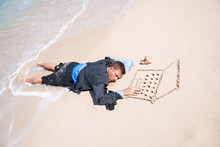 Businessman Falling Asleep Working In Isolation At His Sand Laptop On The Beach With Waves Washing At His Feet