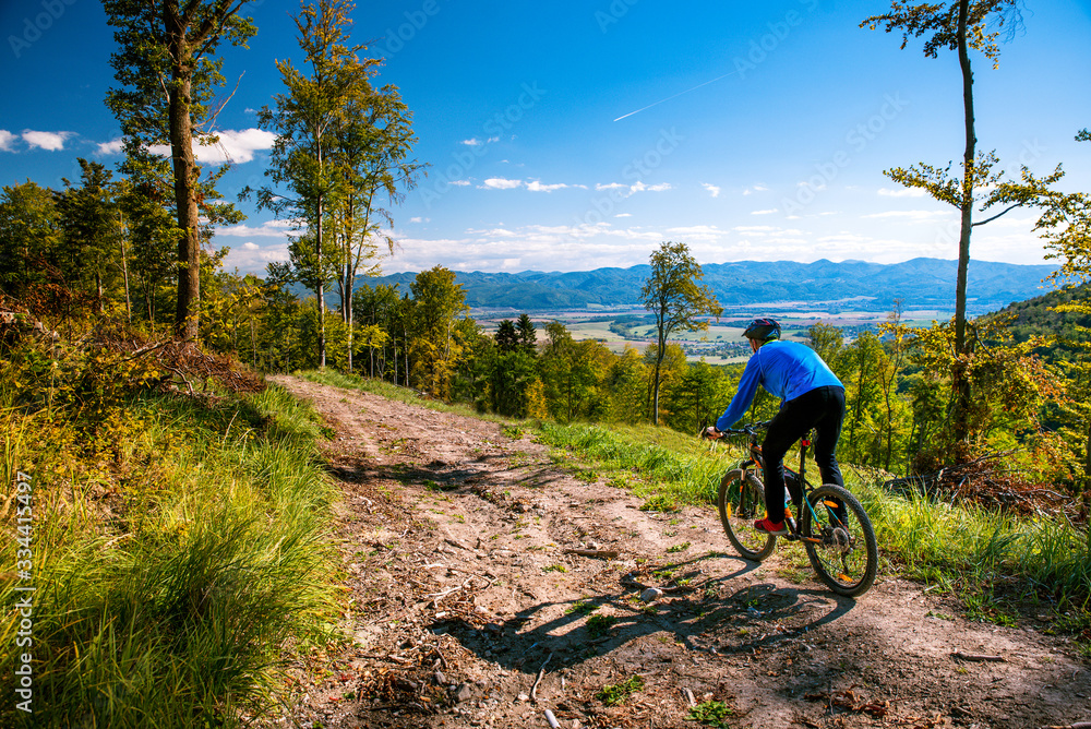 Fototapeta Mountain biking man riding downhill on bike at autumn mountains forest landscape. Outdoor sport activity. Colorful nature.