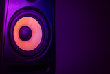 Music studio speaker, with a yellow membrane, isolated on a dark purple background, with space for text on the right side. Electronic music concept