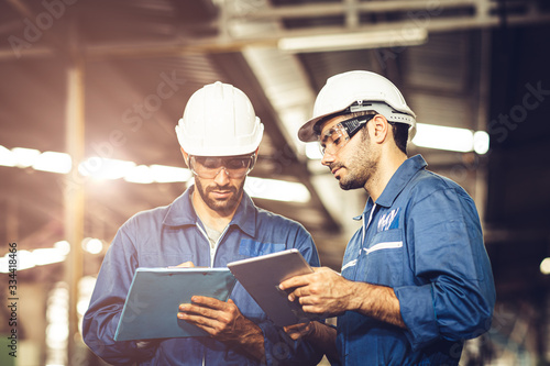 Fototapeta Engineer audit worker working team together with safety uniform and white helmet to work in industry factory handle tablet and checklist