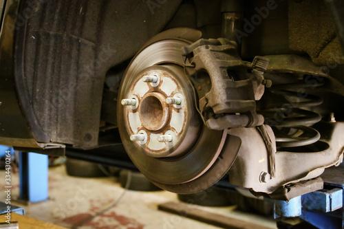 Платно Eje y disco de freno de un vehículo suspendido en un elevador hidráulico de un taller en Madrid, España