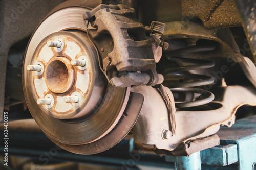 Eje y disco de freno de un vehículo suspendido en un elevador hidráulico de un taller en Madrid, España фототапет