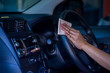 Asian women spry soap and clean car steering wheel with napkin, concept for Coronavirus, Covit-19 prevention and disinfection.