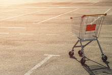 Single Abandoned Empty Shopping Trolley In An Empty Parking Lot Near A Supermarket In The Absence Of People At Sunset.