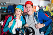 glad girl and guy select gear for hiking and camping in sports shop