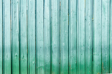 Background in grunge style. Wooden old fence with peeling paint. From vertical boards of turquoise color. With dark vignette around the edges.
