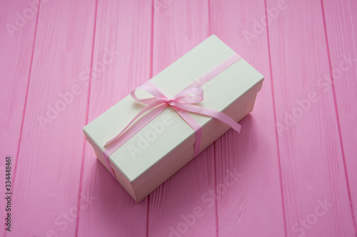 Fototapeta White gift with pink bow. Gift or present box on wooden pink background with copy space. Pastel color. Greeting card. White luxury wedding gift. Valentines day background with gift box. Mother's Day. obraz na płótnie