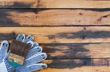 Tool Kit: Paint Brush, Work Gloves On Wooden Background. Repair Your Home Yourself. Gloves And Brush On Old Wooden Boards.