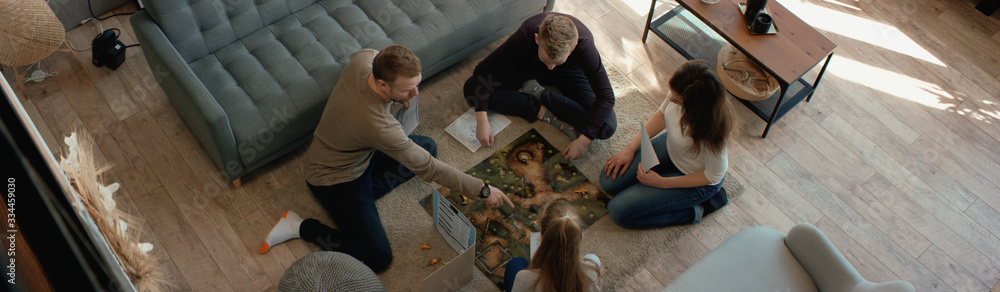 Fototapeta OVERHEAD Family - father, mother and two kids playing a board game together. Stay home, quarantine. Board game is custom made for the shot